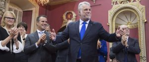Quebec Premier Philippe Couillard stands in front of his new cabinet, during a ceremony, Thursday, January 28, 2016 at the legislature in Quebec City. Caucus president Nicole Menard, from the left, Stephane Billette, whip and Quebec Finance Minister Carlos Leitao, right, stand behind. THE CANADIAN PRESS/Jacques Boissinot